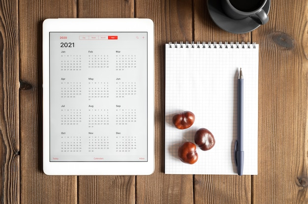 Um tablet com um calendário aberto para 2021 anos, uma xícara de café, castanhas e um caderno de primavera com uma caneta no fundo de uma mesa de tábuas de madeira