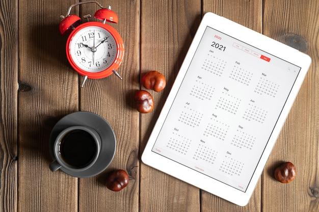 Um tablet com um calendário aberto para 2021 anos, uma xícara de café, castanhas e um despertador vermelho no fundo de uma mesa de tábuas de madeira