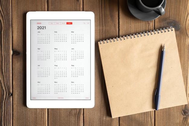 Um tablet com um calendário aberto para 2021 anos, uma xícara de café e um caderno de papel artesanal em um fundo de mesa de tábuas de madeira