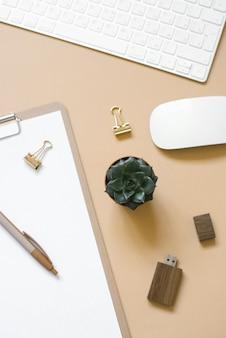 Um tablet com uma folha de papel em branco está em um fundo bege, uma mesa com um computador e suprimentos