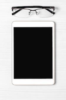 Um tablet com uma tela em branco e óculos em um fundo branco. copie o espaço.