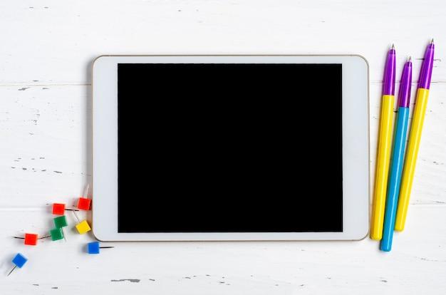 Um tablet com uma tela vazia e material de escritório em um fundo branco de madeira. app de conceito para crianças em idade escolar ou aprendizagem online. copie o espaço.