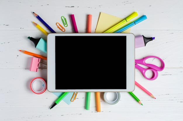 Um tablet com uma tela vazia e material de escritório em uma superfície de madeira branca. app conceito para crianças em idade escolar ou aprendizagem on-line para crianças. copie o espaço