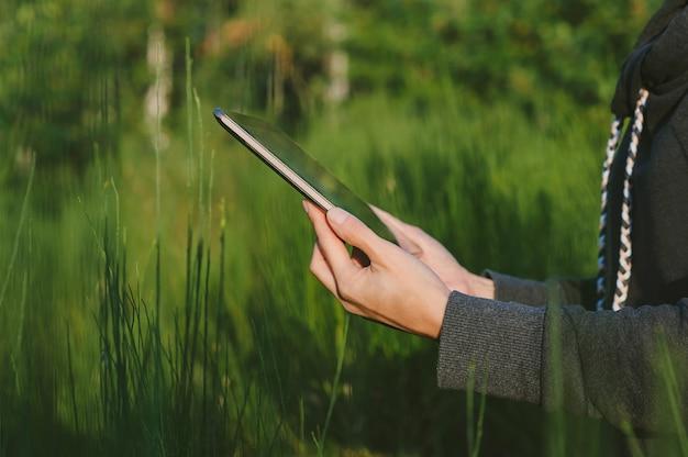 Um tablet nas mãos de um close-up de menina. no contexto da natureza verde.