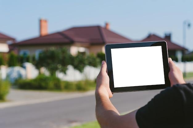 Um tablet nas mãos de um homem, no contexto de uma casa.