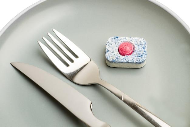 Um tablet para lava-louças em um prato cinza com um garfo e uma faca