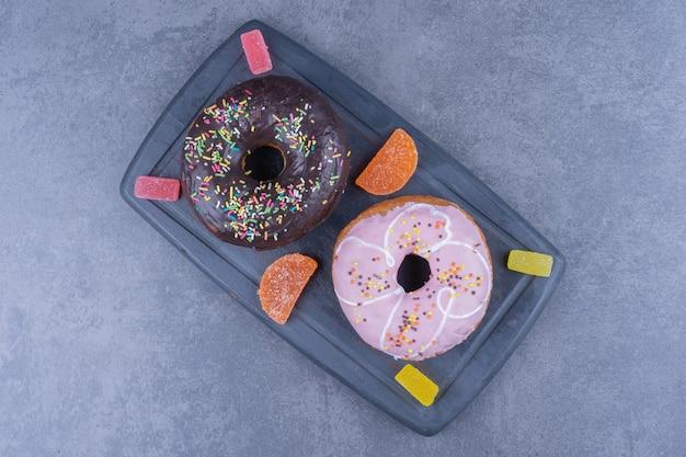 Um tabuleiro escuro cheio de donuts e balas de geleia açucaradas