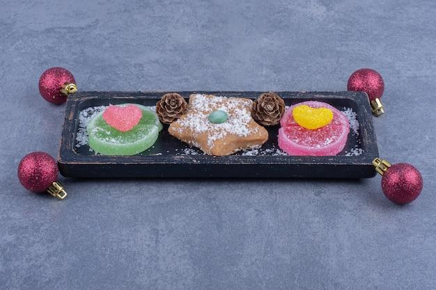 Um tabuleiro escuro com estrela de biscoito e balas de geleia açucaradas