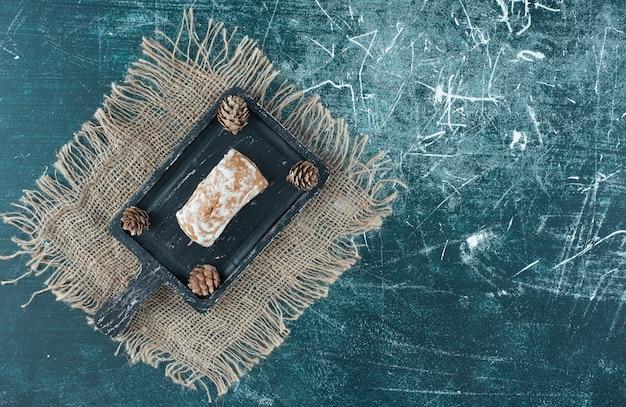 Um tabuleiro escuro com saborosos pães de gengibre e pinhas. foto de alta qualidade