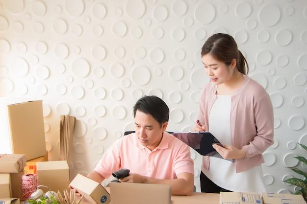 Um tailandês asiático está usando um leitor de código de barras para escanear o número do pacote na caixa do correio.