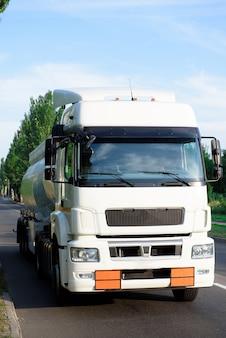 Um tanque de caminhão branco de gasolina dirigindo na estrada.