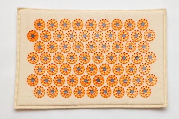 Um tapete de acupuntura laranja para vista superior do tratamento