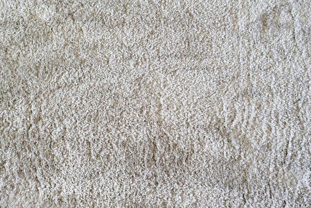 Um tapete de cor branca limpa no chão em casa na sala de estar, textura têxtil