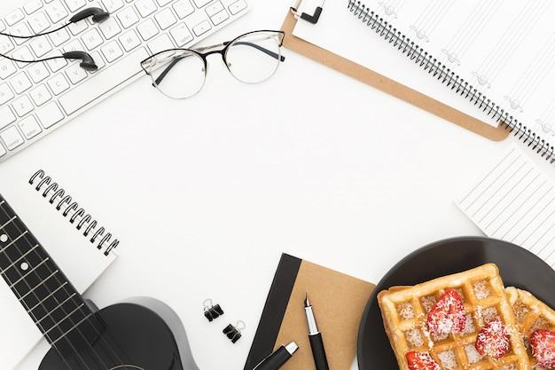 Um teclado, um prato de waffles, óculos, papéis e um violão em uma superfície branca