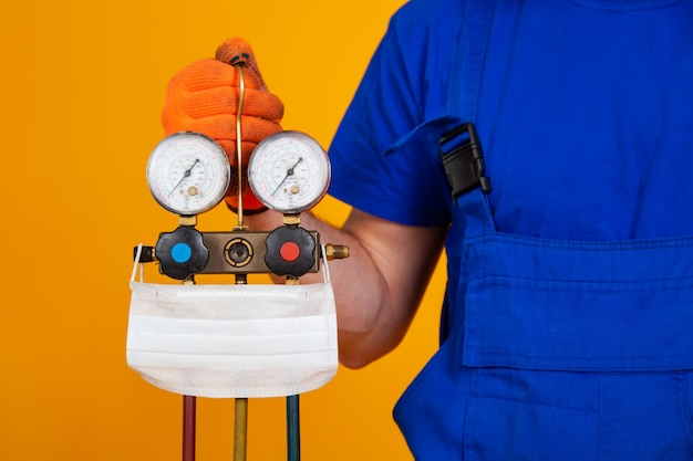 Um técnico de ar condicionado tem manômetros na mão para reabastecer aparelhos de ar condicionado. protetor facial médico em equipamentos de medição para encher condicionadores de ar