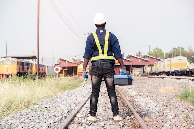 Um técnico de engenharia de máquina africano usando um capacete, bosques e colete de segurança está usando uma chave inglesa para consertar o trem