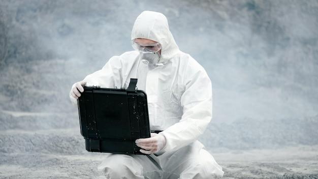 Um técnico de laboratório com máscara e roupa de proteção contra produtos químicos abre uma caixa de ferramentas em terra firme, ao redor de fumaça tóxica.