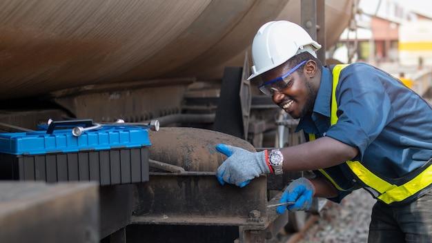 Um técnico de máquinas africano usando um capacete, bosques e colete de segurança está usando uma chave para consertar o gás e óleo do transporte de trem