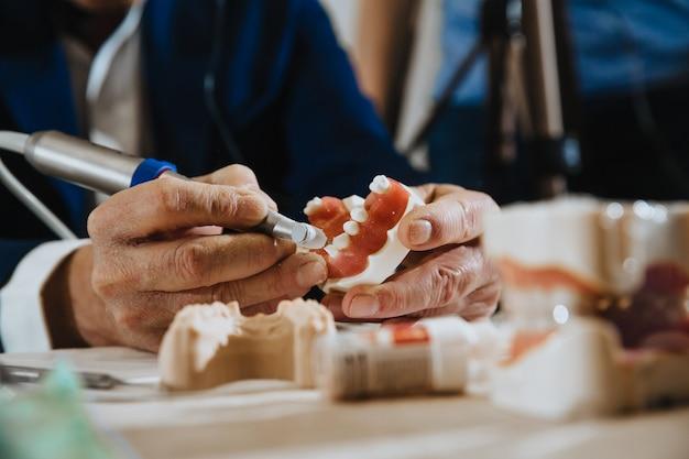 Um técnico de prótese dentária processa um gesso da mandíbula do paciente