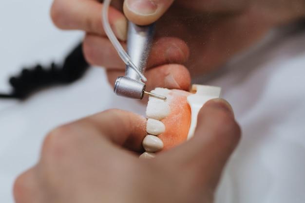 Um técnico de prótese dentária processa um molde da mandíbula