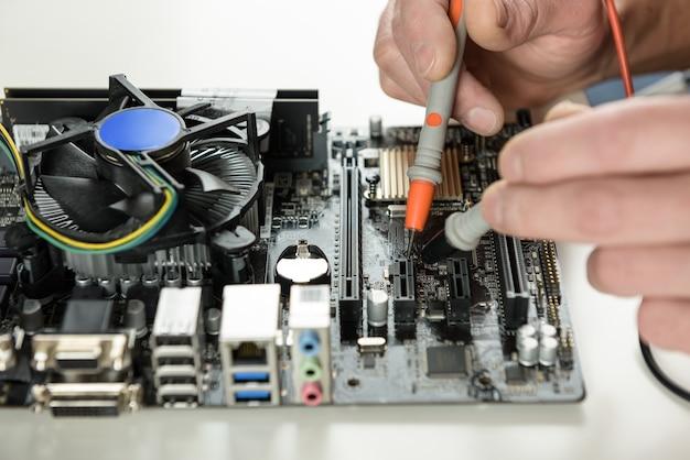 Um técnico verifica a capacidade de manutenção da placa-mãe do computador de perto
