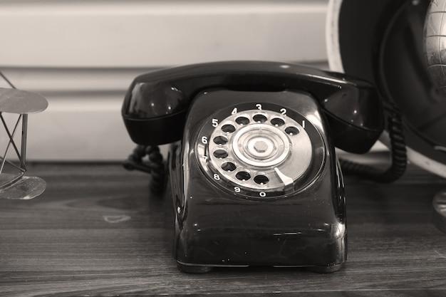 Um telefone antigo com botão giratório, foto sépia