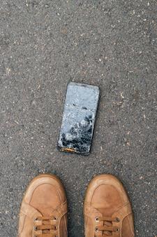 Um telefone celular caiu no chão com o dono olhando para o telefone com a tela quebrada.