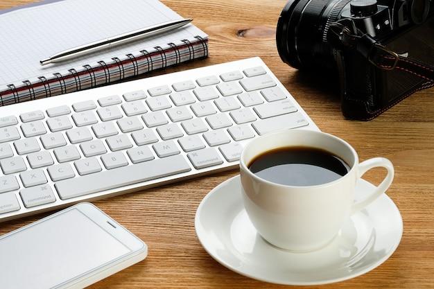 Um telefone celular, um teclado de computador, uma caneta e o bloco de notas para anotações, uma caneca de café e uma câmera na mesa de madeira.