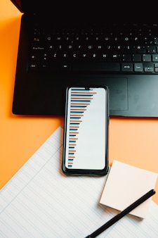 Um telefone com estatísticas sobre um fundo laranja com laptop e notebook com conceito financeiro
