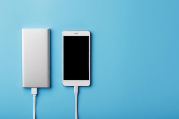 Um telefone de carregamento com powerbank sobre fundo azul. mantenha a bateria carregada no seu dispositivo de qualquer maneira.