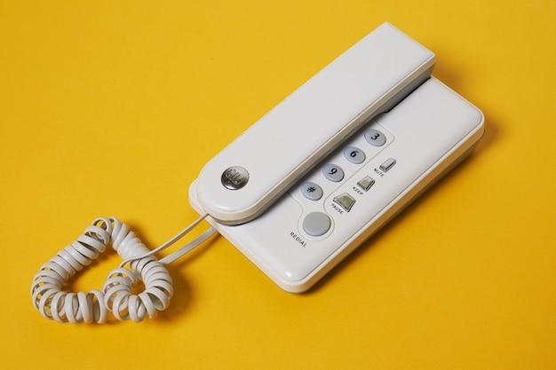 Um telefone fixo branco em amarelo