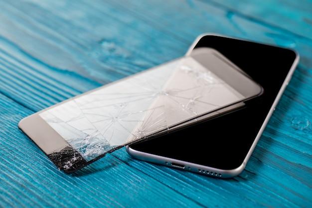 Um telefone móvel preto é tela quebrada no fundo de madeira.
