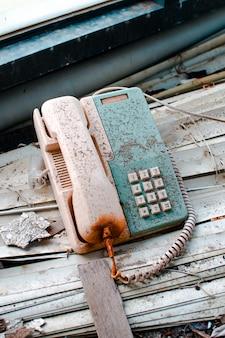 Um telefone velho e enferrujado dentro de um prédio abandonado em wanli ufo village, taiwan