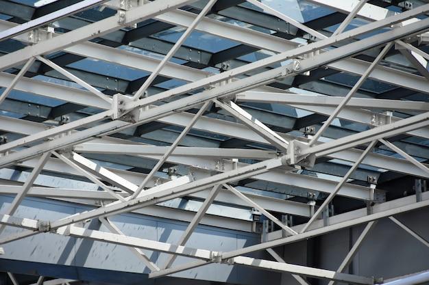 Um telhado feito de grandes estruturas metálicas e um vidro de um edifício moderno