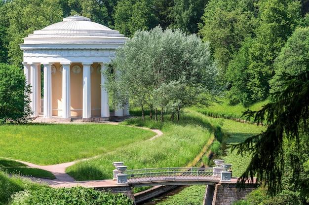 Um templo de estilo clássico em um belo parque de verão campo verde com flores brancas e amarelas ao ar livre na natureza no verão. campo de verão verde brilhante durante o dia