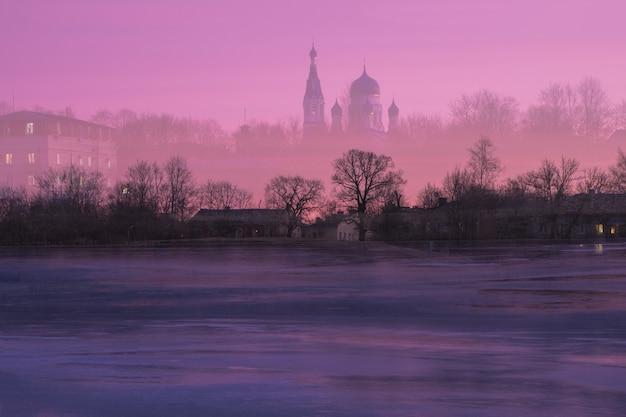 Um templo místico no céu. dupla exposição da paisagem do templo no contexto de um amanhecer de inverno roxo.