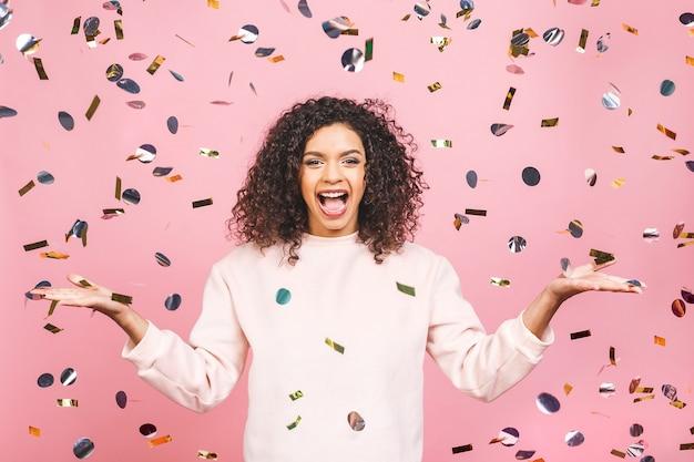 Um tempo mágico - retrato de uma jovem afro-americana muito feliz com os braços abertos, sorrindo para confetes caindo isolados contra rosa.