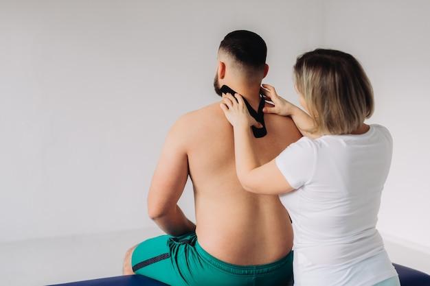 Um terapeuta gravando fita de cinesiologia no pescoço do paciente.