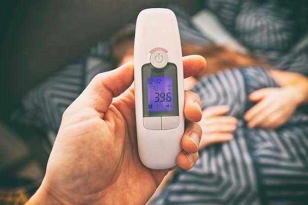 Um termômetro na mão de um homem que mostra alta temperatura em sua esposa