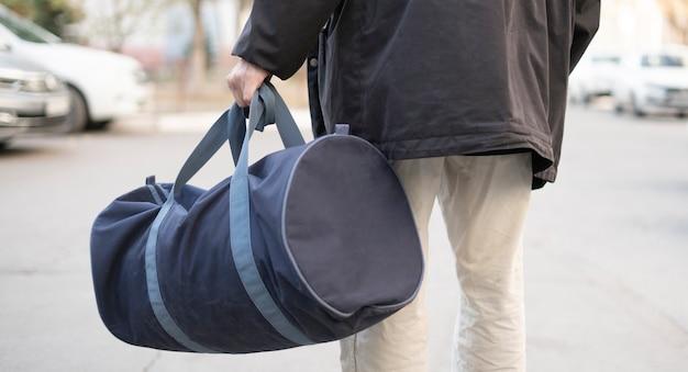 Um terrorista segurando uma bolsa com uma bomba dentro para colocá-la em um lugar público na rua