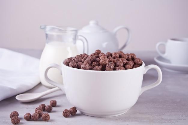 Um, tigela, de, secos, chocolate, bolas, cereal, e, garrafa, se, leite, ligado, a, cinzento, tabela, para, saúde, pequeno almoço