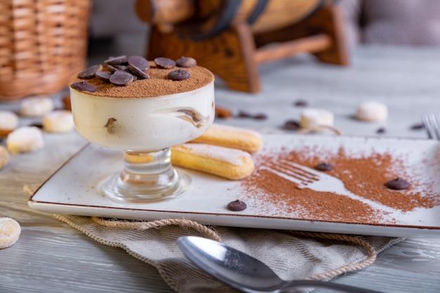 Um tiramisu italiano clássico de sobremesa em uma tigela com uma porção atmosférica de chá.