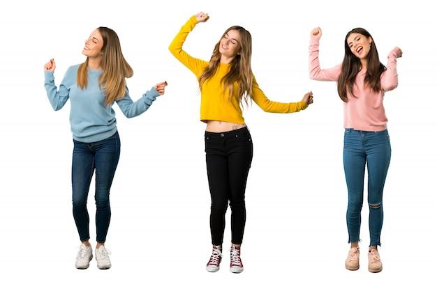 Um tiro completo de um grupo de pessoas com roupas coloridas gosta de dançar