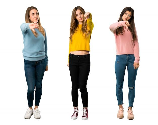Um tiro completo de um grupo de pessoas com roupas coloridas, mostrando o polegar para baixo