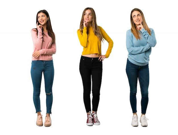 Um tiro de corpo inteiro de um grupo de pessoas com roupas coloridas, pensando uma idéia enquanto looki