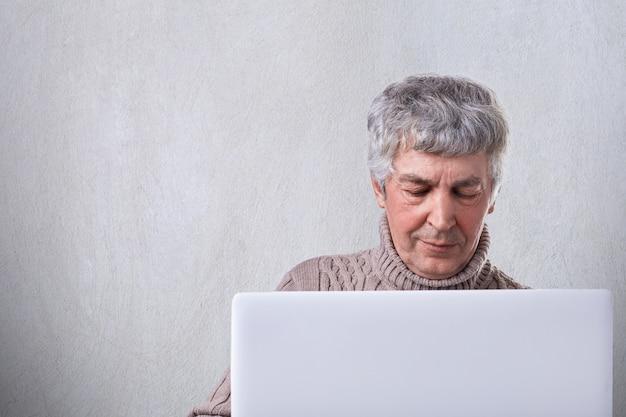 Um tiro de homem mais velho, com cabelos grisalhos e rugas no rosto, olhando para a tela