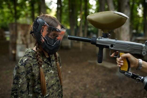 Um tiro de uma arma de paintball na cara da garota na máscara, parque infantil na floresta no fundo. esporte radical com arma pneumática e balas ou marcadores de tinta, jogo de equipe militar ao ar livre