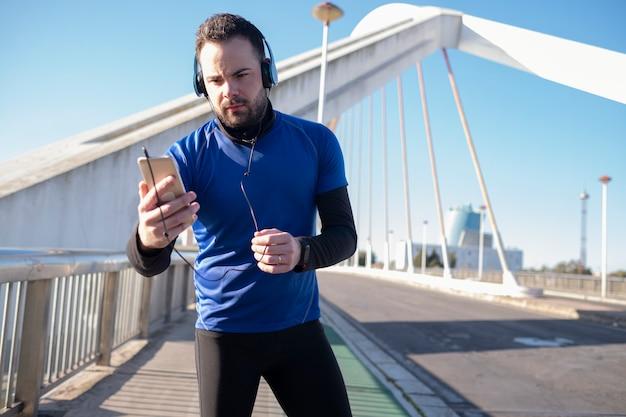 Um tiro do close up de um homem em fones de ouvido azuis usando seu celular enquanto jogging na rua
