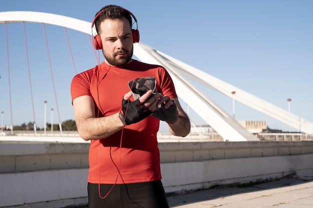Um tiro do close up de um homem em fones de ouvido vermelhos usando seu celular enquanto jogging na rua