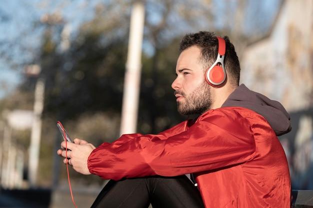 Um tiro do close up de um jovem macho no fone de ouvido vermelho, ouvindo música enquanto trabalhava na rua
